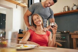 Man and woman relax in the kitchen while giving a massage and drinking wine.